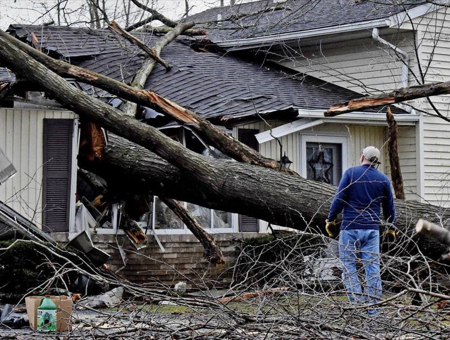 A man watching a house damaged by a fallen tree after a storm.