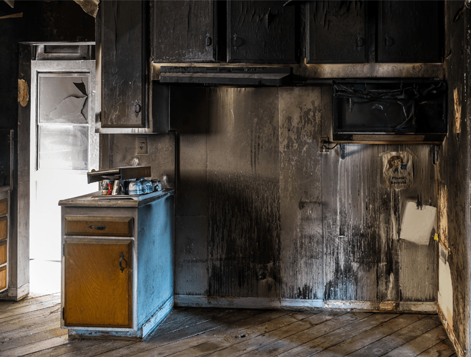 Kitchen room showed after fire damage with soot all over half burnt cabinets