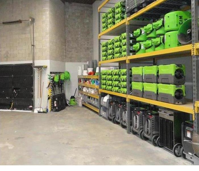 warehouse interior with green equipment loaded on shelves